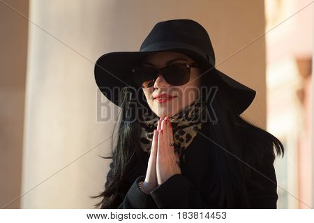 Young woman praying in a big hat