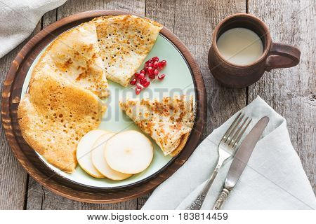 Tasty traditional russian breakfast of pancakes with honey on plate. Rustic style. Space for your text.