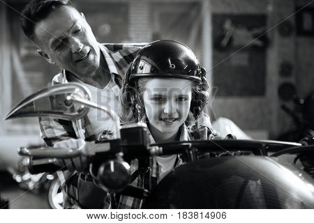 Little biker. Energetic adventurous attentive dad putting a helmet on his childs head for making it feel like a real ride