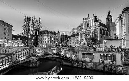 Romantic Ljubljana's city center in black and white: river Ljubljanica, Triple Bridge - Tromostovje, Preseren square and Franciscan Church of the Annunciation. Ljubljana, Slovenia, Europe.
