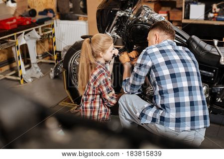 Quality time. Experienced nice amateur tinker explaining his child which problems he seeing while teaching her about his job
