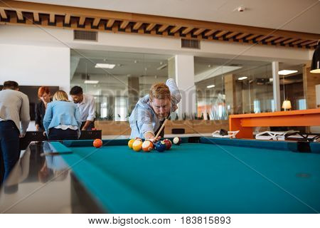 Handsome ginger man playing billiard in the office.