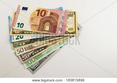Us Dollar Bills And Euro Bills Spread Mixed On White Background.