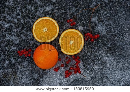 Cut oranges and branches with a viburnum on ice