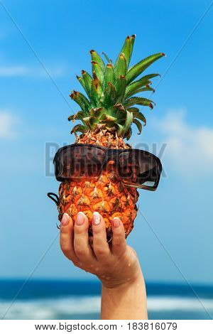 Pineapple on blue sky background. The concept of a tropical summer holiday.