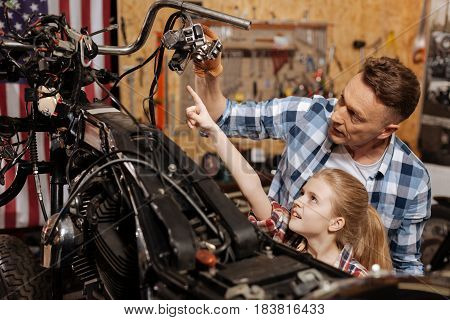 What those things do. Smart eager lively kid wanting knowing what her dad repairing while spending time at his garage