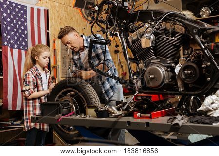 Expert dad. Gifted competent able mechanic explaining his child how separate part of the bike working while she spending time at his garage