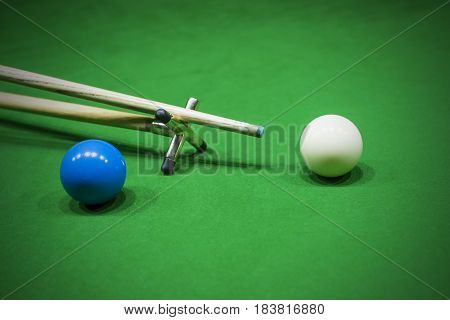 Snooker table. Aiming the cue ball with spider stick.