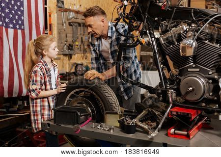 Dedicated man. Charming adorable engaged child spending time with her father and assisting him while he trying teaching her a little