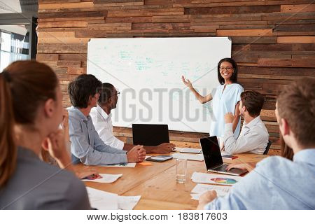 Young black woman giving business presentation at whiteboard