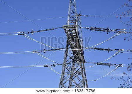 A transmission tower or power tower (electricity pylon) with power lines against a blue sky showing the connection and the isolation from the steel construction picture from the North of Sweden.