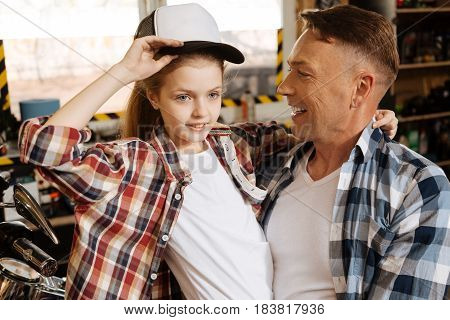 Adorable dads daughter. Stunning pretty young lady looking adorable wearing dads hat while he holding her up in his arms