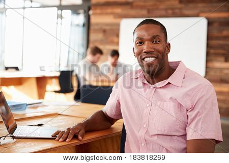 Smiling young black man in creative office looking to camera
