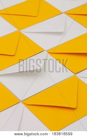 Composition with white and yellow envelopes on the table.