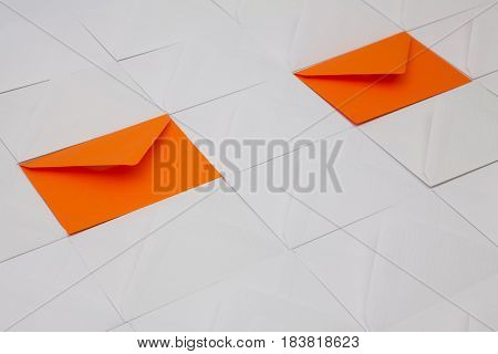 Composition with white and orange envelopes on the table.