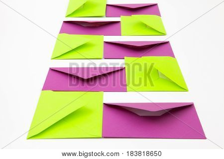 Composition with purple and green envelopes on the white table.