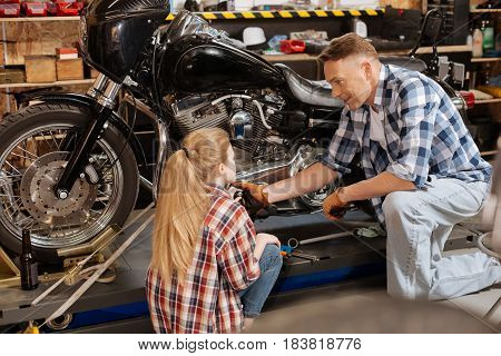 This part is important. Inventive talented skilled mechanic teaching his daughter about the way the bike working while she listening attentively