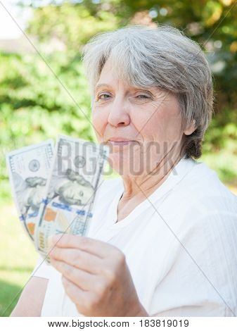 Senior woman holding 200 us dollars
