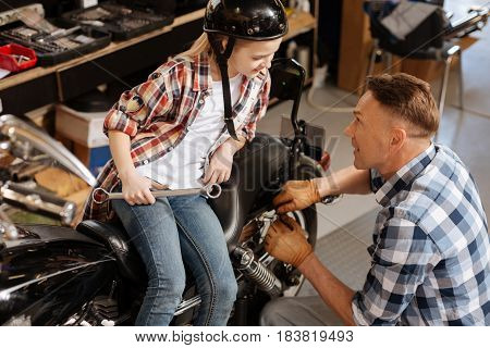 Motivated beautiful lively girl wanting assisting her dad in fixing the bike while sending the day at his garage