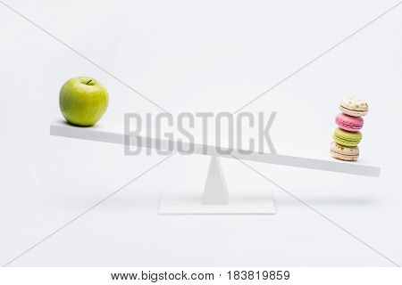 Close-up View Of Apple And Macarons Balancing On Seesaw, Healthy Living Concept