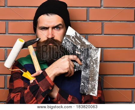 Bearded Foreman Holding Various Building Tools With Serious Face