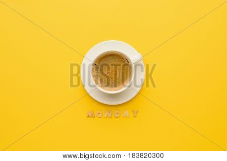 Top View Of Cup Of Espresso Coffee And Monday Lettering Isolated On Yellow