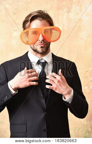 Manager in elegant black business suit posing with funny orange big party glasses