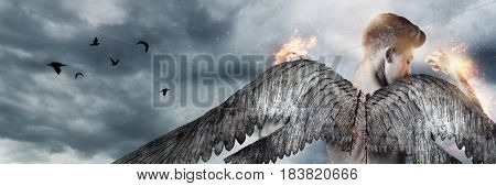 back of strong angel with wings in fire in front of grey clouds