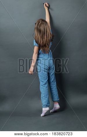 young girl on tiptoe writing at grey background