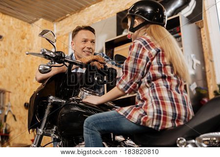 Engaged in conversation. Engaged charmed great father listening to what his daughter saying while leaning on a bike she sitting on