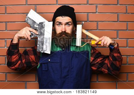 Bearded Painter Man Holding Various Building Tools With Surprised Face