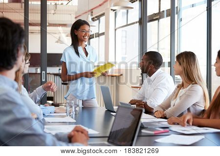 Young black woman holding document addresses team at meeting