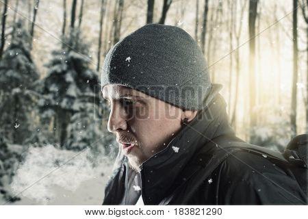 hiker breathe out in front of blurred forest landscape