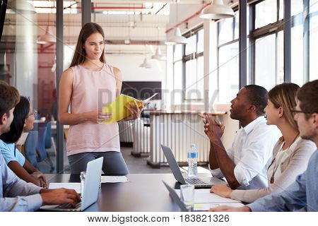 Serious woman with document stands addressing team meeting