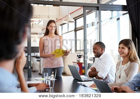 Happy woman with document stands addressing team at meeting