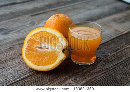 orange and a glass of juice sitting on table of dark wood, full of vitamins