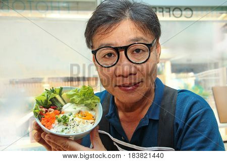 Thai jasmine rice in Japanese styleChef holding a bowl of rice is topped soft boil eggs and fried chicken with garlic chives Oyako Donburi.