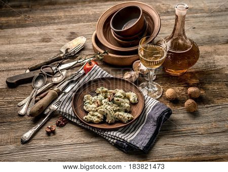 Delicious pasta with sauce of nuts served with some wine, antique dishware, blue squared napkin