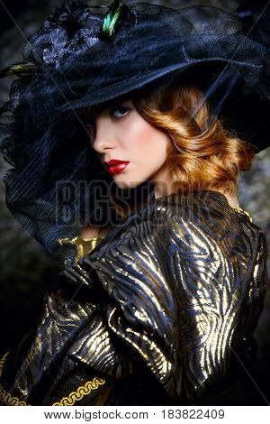 Fashion shot of a stunning young woman in luxurious dress and elegant hat over vintage background. Headwear style.