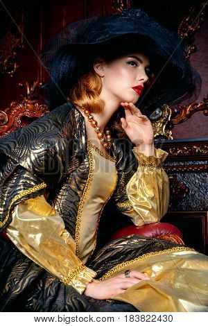 Portrait of a beautiful young woman in the lush expensive dress and elegant broad-brimmed hat in an old palace interior. Vintage style. Fashion. Renaissance Style.