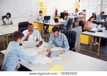 Three men working together in a busy office, elevated view