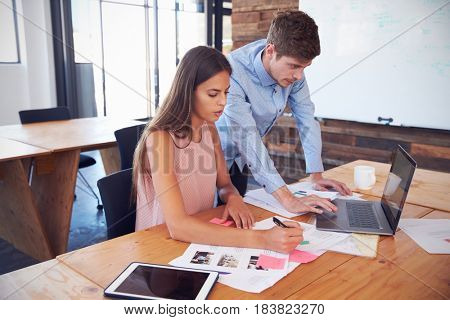 Man and woman working together at a desk in an office