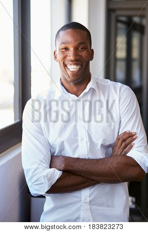 Young black man with arms crossed smiling, vertical portrait