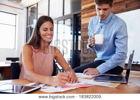 Man sitting on a woman's desk in office, as she takes notes