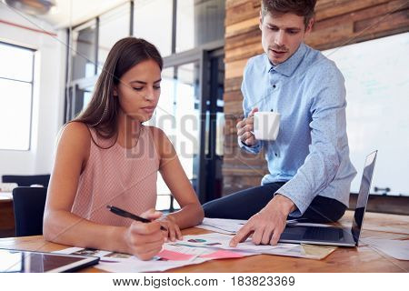 Man sitting on a woman's desk discusses work with her