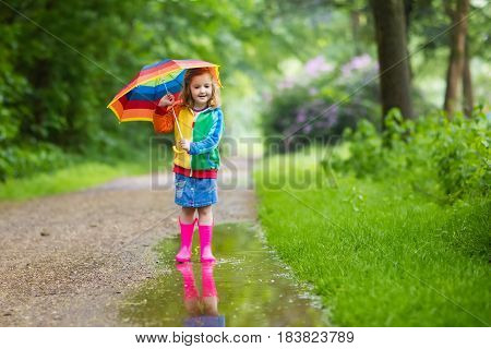 Child Playing In The Rain With Umbrella