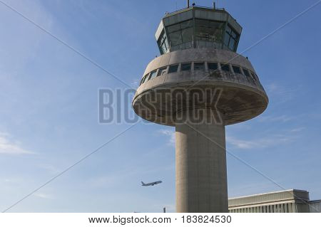 A Plane Flies Next To The Control Tower At Barcelona Airport, Spain