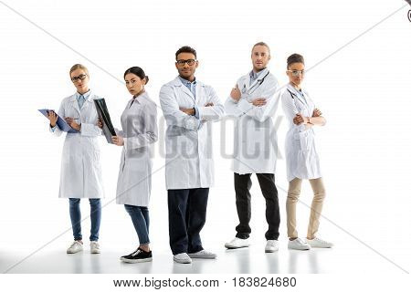 Group Of Young Confident Professional Doctors In White Coats Standing Isolated On White