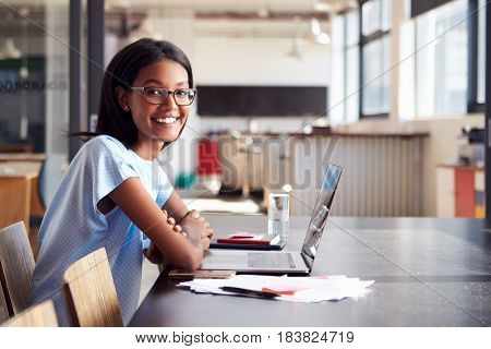 Young black woman in office with laptop smiling to camera