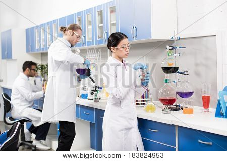 Group Of Young Professional Scientists Making Experiment In Research Laboratory